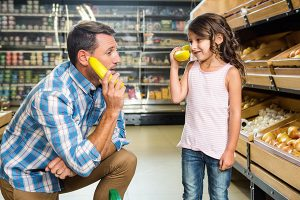 Dad playing with daughter at grocery store